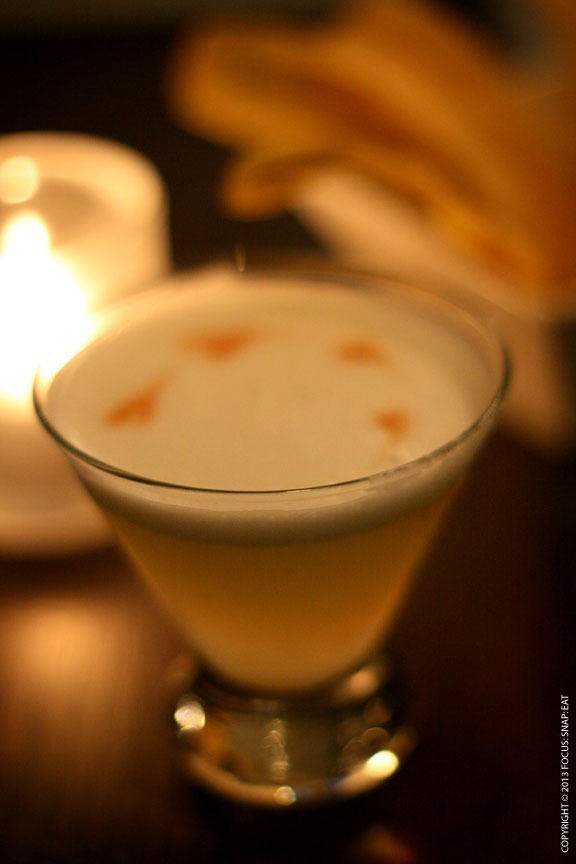 The classic Pisco Sour, made of pisco with egg whites dotted with Angostura bitters. Served up with some plantain chips.