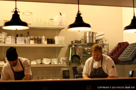 Chefs working out of the tiny open kitchen in front of the counter seating