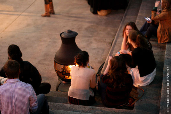 People sat around the glow of a wood-burning pit in the cool evening air