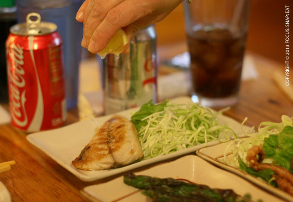 Adding lemon to the grilled mackeral (or saba shio)