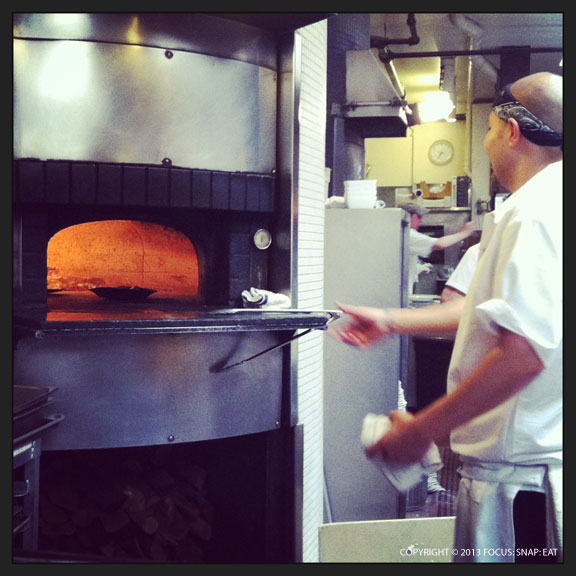 Pizza and dishes like roasted asparagus get cooked in the wood-fire oven