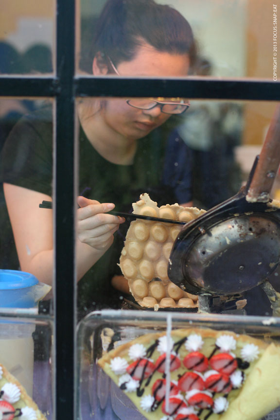 "An employee works the ""egg puff"" station. This is like a bubbly waffle."