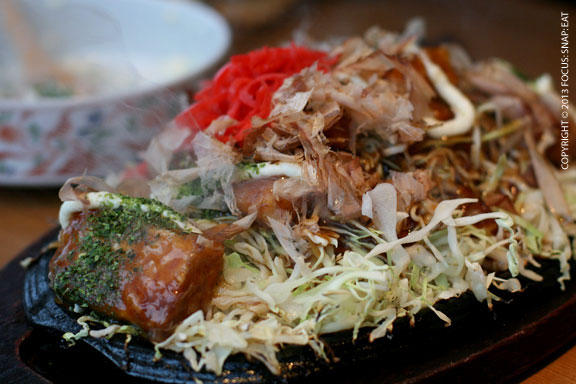 Okonomiyaki ($12) was a sizzling platter of tofu and topped with bonito flakes and red ginger, on a bed of cabbage