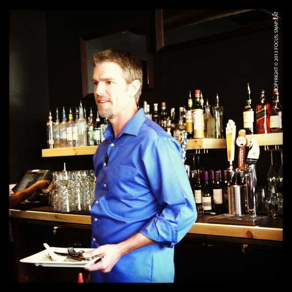 The new manager of Umami Oakland chatting up the customers at the bar