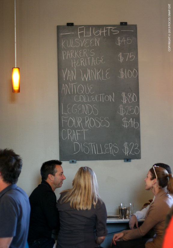 A board listed tasting flights of whiskey and bourbon that's offered at Hard Water