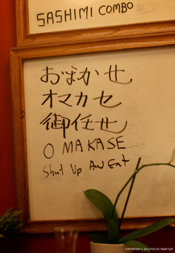 """A board listed the different ways to write """"omakase"""" in Japanese. The English version shows the owner's character, saying that omakase meant """"shut up an eat"""""""