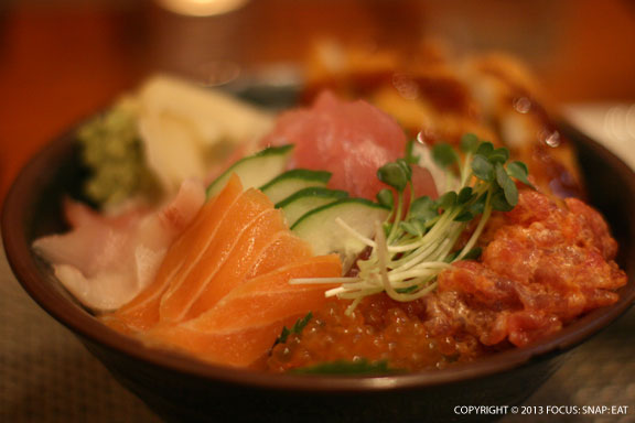 Sushi Bowl ($21.95), chirashizushi style bowl with fresh ahi, hamachi, house-cured salmon, ahi tartar, and ikura, served with fried calamari and garnished with chiso and pickled ginger.