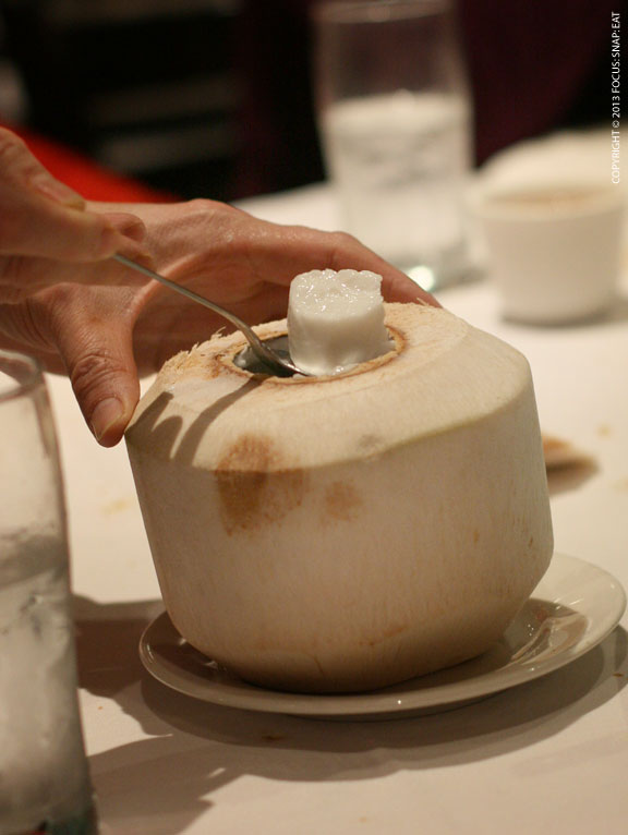 Scooping up coconut pudding from a coconut husk.