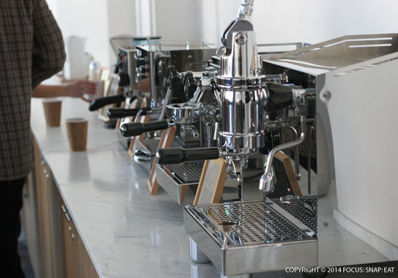 These a row of fancy espresso equipment almost like an exhibit