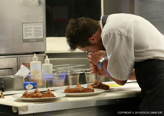 A chef in the kitchen of Cumulus Up putting the finishing touches on the popular duck waffle with foie gras