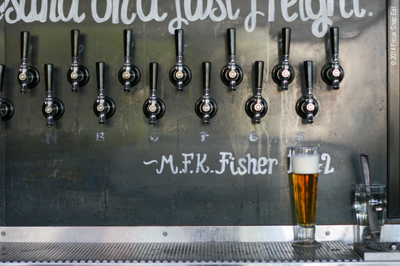 The whimsical bar includes beer quotes and this wall of cool handles pouring a list of 33 local craft brew.