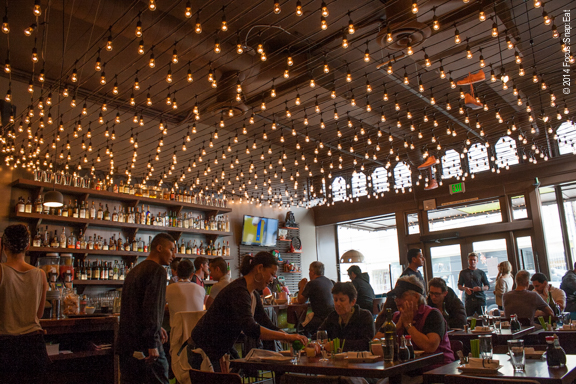 The festive environment is highlighted by the ceiling of stringed light bulbs, making one feel like you're dining in the backyard of a summer party.