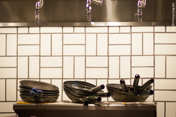 Woks seen at the open kitchen waiting for some action.