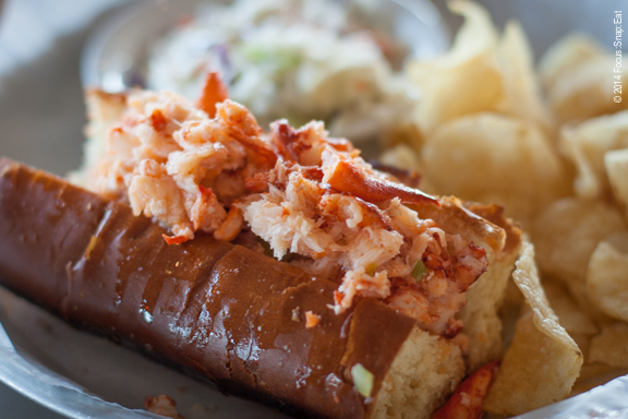 The popular lobster roll ($22.95) tossed simply in butter in a brioche roll served with potato salad and chips.