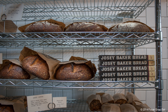 Fresh bread made from hand-ground flour is sold from a rack, along with Baker's new book on bread-making.