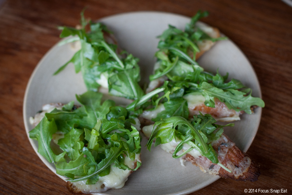 Garlic cheese toast with gruyere cheese and topped with arugula salad, $7