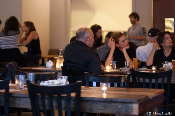 The open dining room with communal tables, making it a great place for family dinners.
