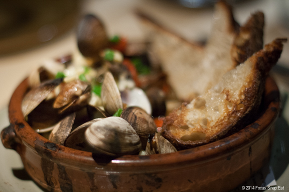 Wood-oven clams with sweet corn, shishito peppers, cherry tomatoes, scallions, and sake butter ($19)