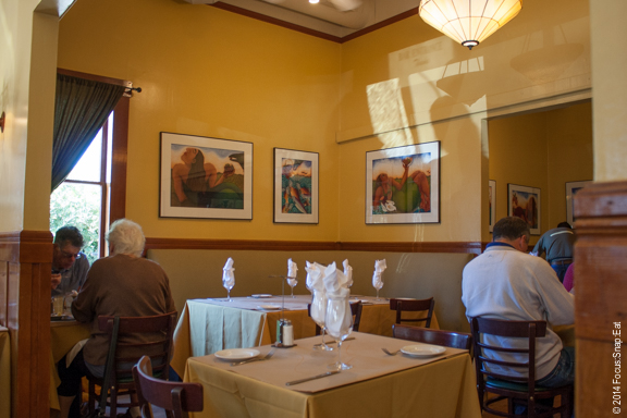 The brightly lit dining room with local artwork like dining in a refurbished house.