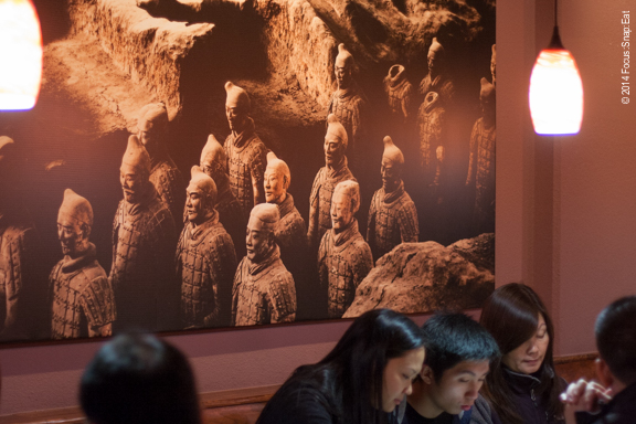 The dimly lit restaurant with ambient lighting has one wall with a large photo of the restaurant's namesake, the terra cotta warriors or Xian.