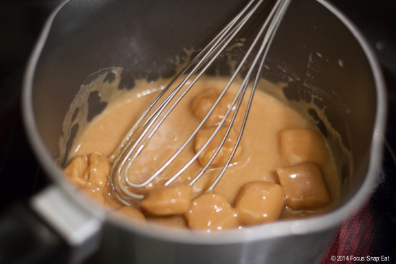 Melting caramel cubes to make the sauce to drizzle on the cookies.