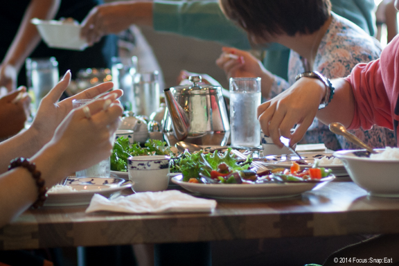 I like taking shots of big tables to give a sense of the dining experience. Here it helped that the backlight from the window created a nice glisten to the glassware. Then I cropped into close to focus on the activity and not the people.