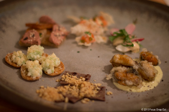 A complimentary platter of little bites before dinner is eaten with your hands or a toothpick. They included fried mussels, apple fritters, house-made jerky, and salmon roe on a crisp.