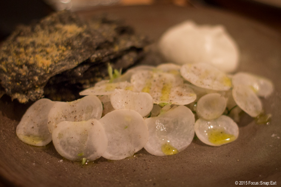 The halibut as it came to the table with a tent of thinly sliced radish and accompanied by squid ink crackers.