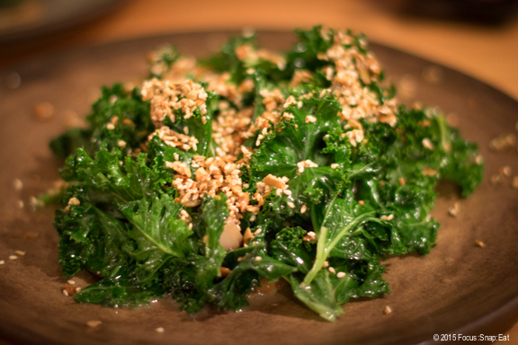 Wild mushrooms and kale with local wakame kraut. The mushrooms are hidden under the kale with sesame seeds.