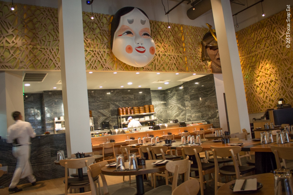 The sushi bar in the spacious dining room has a large Japanese mask hanging above.