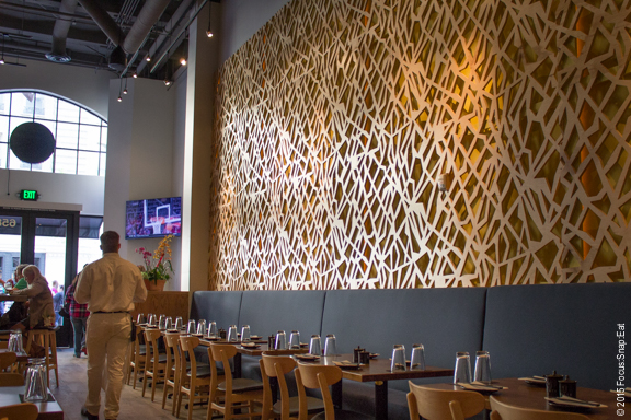 The large wall with high ceilings is decorated with a lattice wood design.