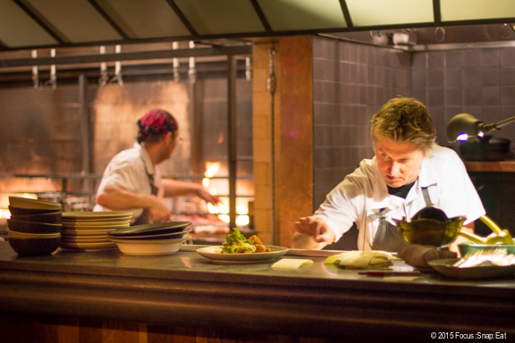 Chefs working at the open kitchen with wood fire in the back.