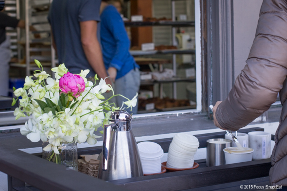 Baristas deliver coffee from a window.