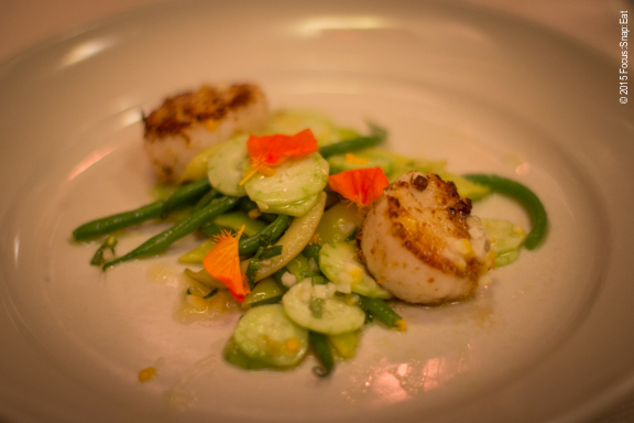First course of seared sea scallops with cucumber, green bean, anise hyssop salad, Meyer lemon and nasturtiums.