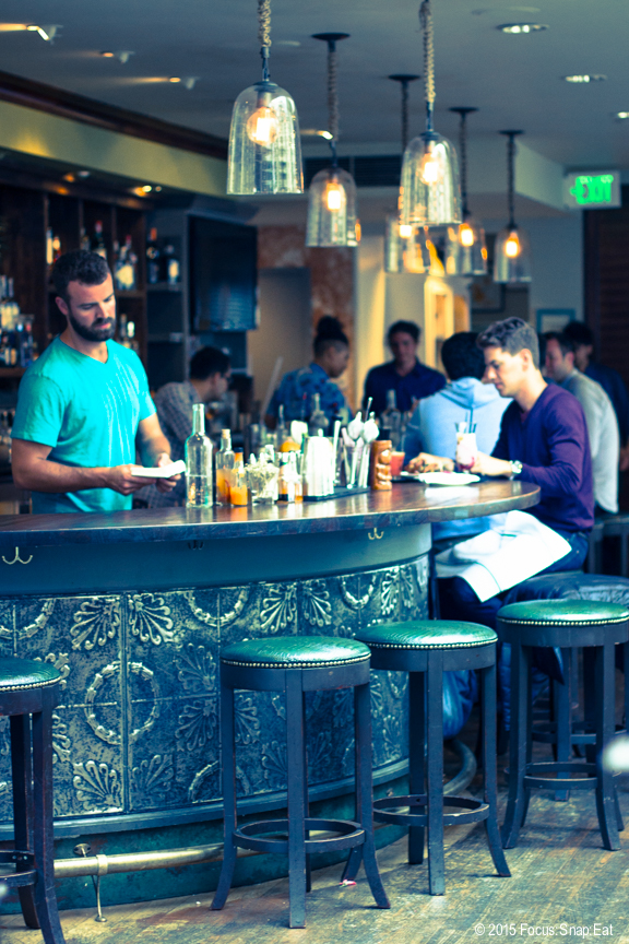 The large bar is at the center of the restaurant and is often bustling.