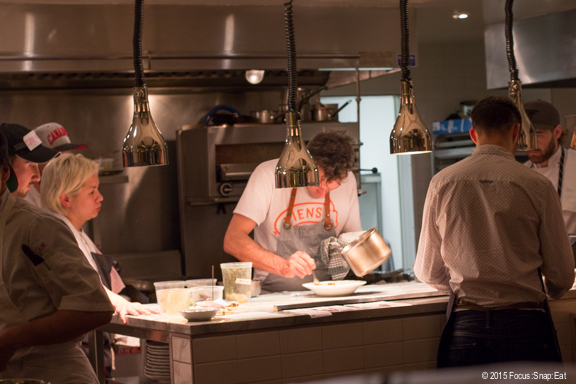 His face obscured by the ambient light, but that's Chef Antoine-Charles Crete in the large open kitchen.