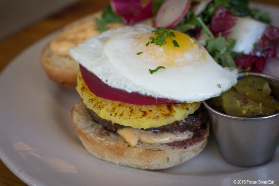 World Famous Five Leaves Burger, $16, with grilled pineapple, pickled beet, harissa mayo, sunny side up egg