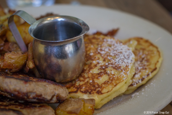 A portion of The Plow, a sampler platter. Show here are two lemon ricotta pancakes.