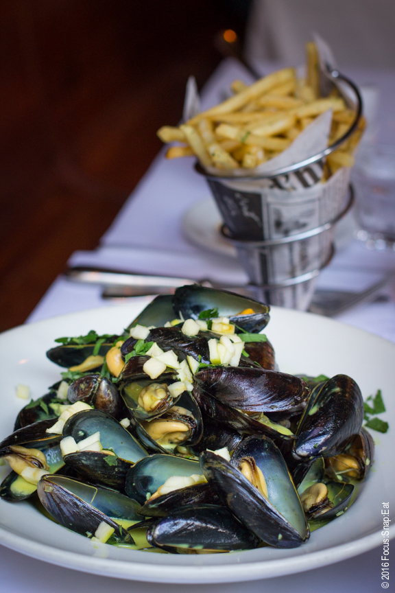 Steamed mussels in white wine, curry and apples sauce with cornet of fries