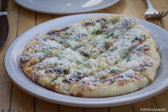 Chargrilled focaccia with parmesan, herbs and garlic oil.