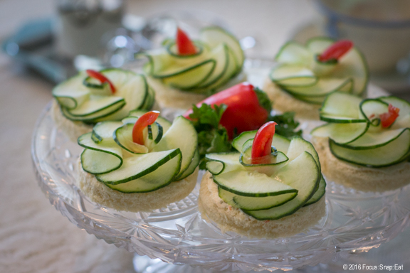 Cucumber tea sandwiches creatively presented as flowers reminiscent of those found in the garden.