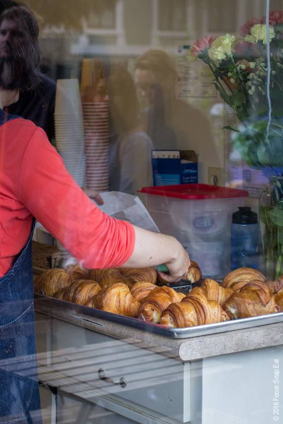 Freshly baked croissants seen through the window.
