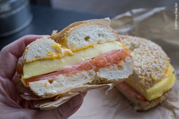 Combo smoked salmon with egg and cheese sandwich on a sesame bagel.