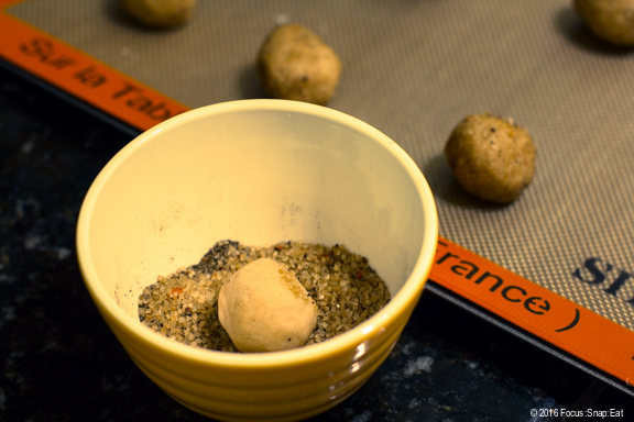 Rolling the snickerdoodle dough balls in mix of sugar and chai spices