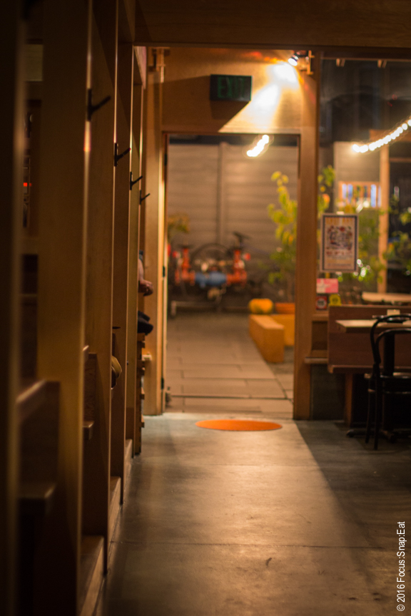 The front of Izakaya Rintaro includes a long counter bar and several booths.