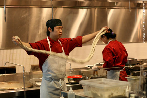 The noodle chef pulling fresh noodles for the day
