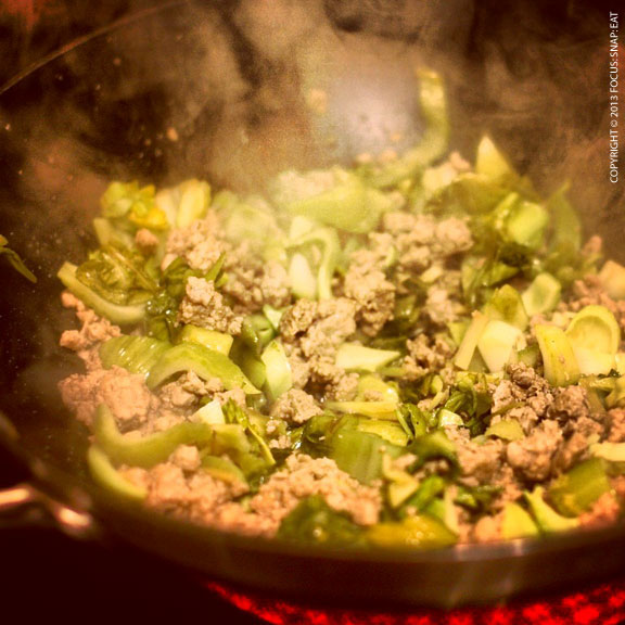 Frying up the ground pork with pickled vegetables