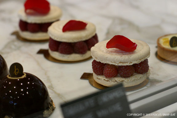 Lovely grande macaron with rose creme mousseline, raspberries, vanilla powder and rose petal