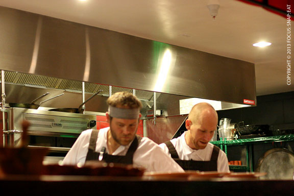 Chefs working at the open kitchen at the center of the restaurant
