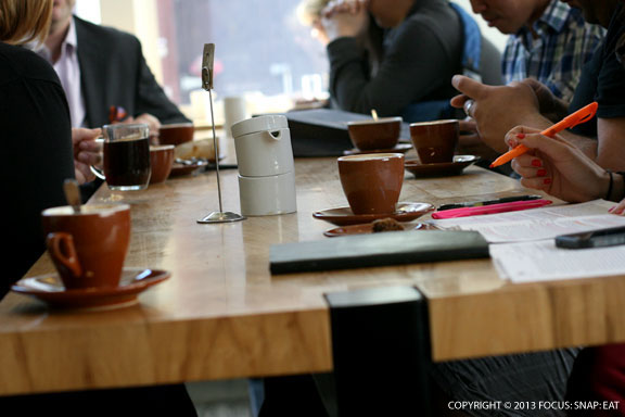 A big communal table takes up most of the cafe with additional bar seating along the wall